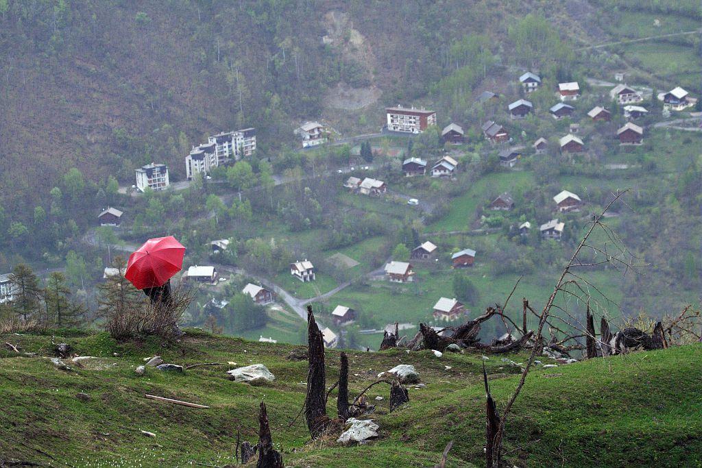 Un randonneur avec son parapluie face au hameau des Claux de Pelvoux. ©Jean-Philippe Telmon - Parc national des Ecrins