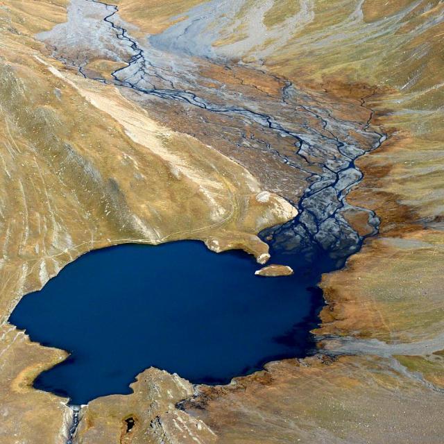 Les tresses du torrent de Maurian rejoignent le lac du Goléon, grande tâche d'encre bleue sur l'étoffe roussie des alpages (pris depuis le col des 3 Evêchés) © Hélène Quellier - Parc national des Ecrins