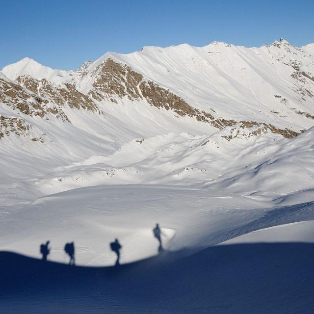 Skieurs de randonnée en ombre portée au vallon de La Pousterle, au fond le Barle - Réallon ©Mireille Coulon - Parc national des Ecrins